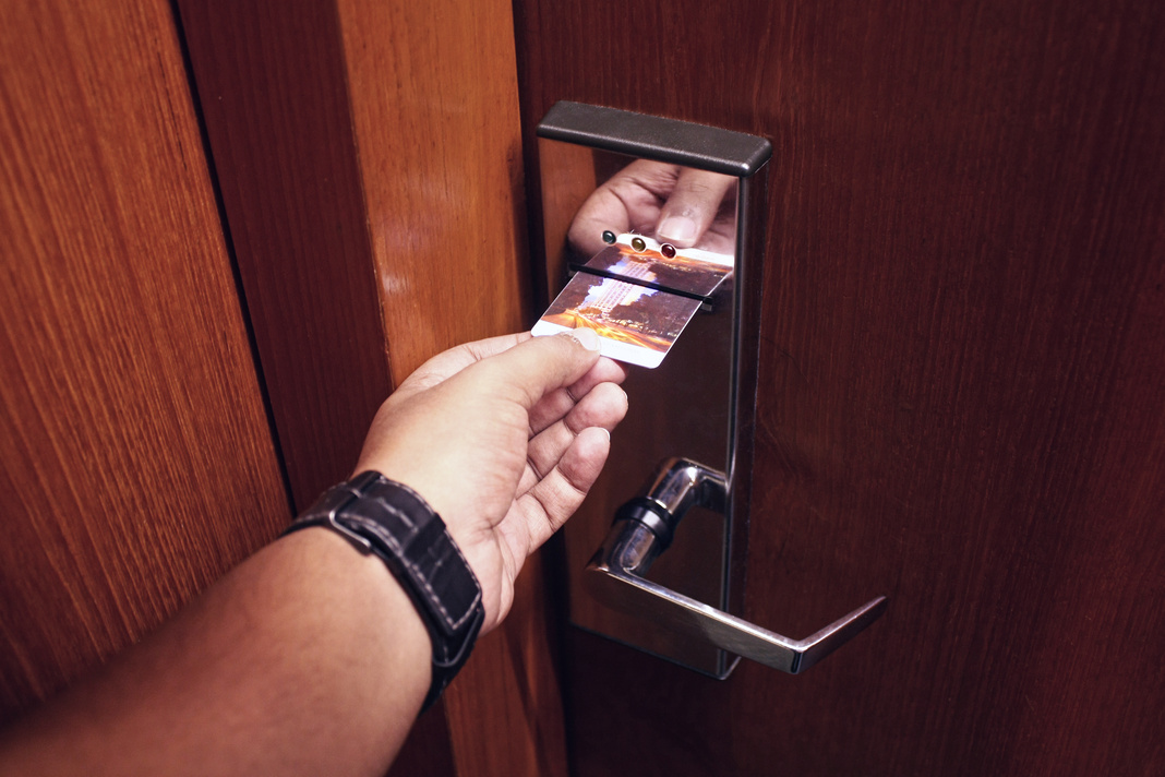 Man inserting key card on a hotel room's electronic access control system